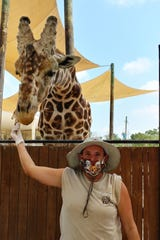 Naples Zoo keeper Cindy Watson poses with a giraffe. All of the zoo's caretakers have started wearing face masks around the animals.