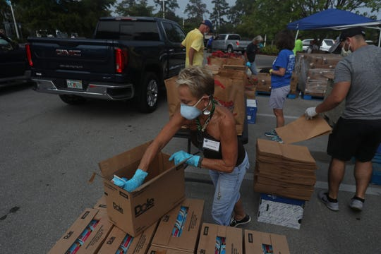Employees and volunteers for the Harry Chapin Food Bank work a mobile food pantry in Immokalee.