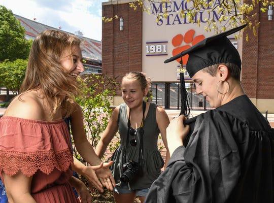 Clemson University graduating senior Ellen Wilkins, left, smiles with Caroline Buck, middle,  and fellow graduating friend Katie Bolen outside Memorial Stadium in Clemson Tuesday.