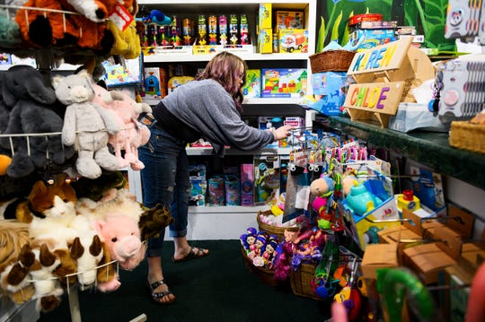 Dani Knox puts a toy back on the display at the Elephant's Trunk Tuesday, April 21, 2020. The toy store reopened after Gov. McMaster's order for some retail stores to reopen.