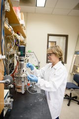 Sarah Harcum growing cells to make proteins out of the bioreactors in her lab.