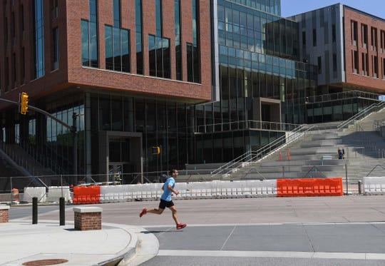 A jogger runs by the nearly finished College of Business at Clemson University Tuesday, as spring semester wraps up and moves into a summer session.