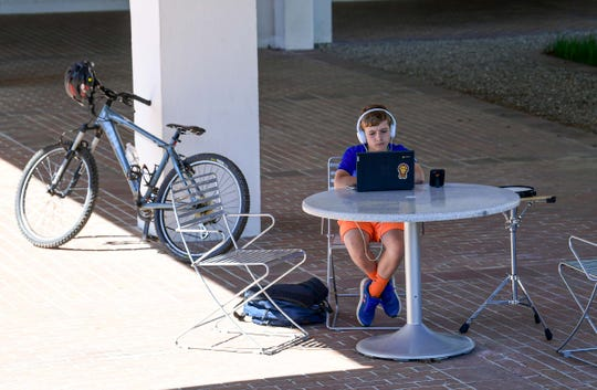 Andrew Connelly of Clemson works on his homework from R.C. Edwards Middle school, sitting outside the Cooper Library at Clemson University, since her internet is not working at home. Clemson Spring semester students are finishing classes online too, and some will take online classes for a summer session.
