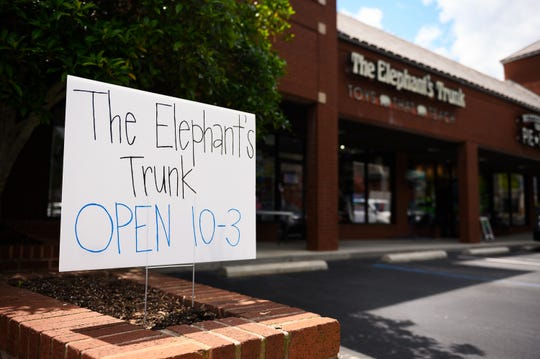 A sign indicating the Elephant's Trunk's hours is displayed in front of the store Tuesday, April 21, 2020. The toy store reopened after Gov. McMaster's order for some retail stores to reopen.