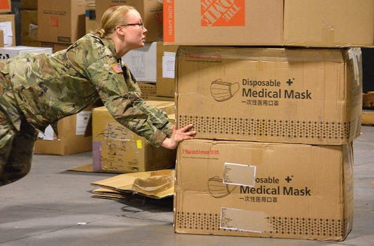 Hannelora Wald of the Montana National Guard moves boxes filled with personal protective equipment Tuesday, while preparing medical supplies to be sent to health care workers around the state.