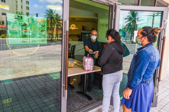 Manager Johnny Lee, left, presents a couple of complimentary face masks to Guam Memorial Hospital co-workers Janelle Santos, center, and Dusty Perez, as the two pick up their take-out order at Lee Garden in Tumon in this April 21 file photo.