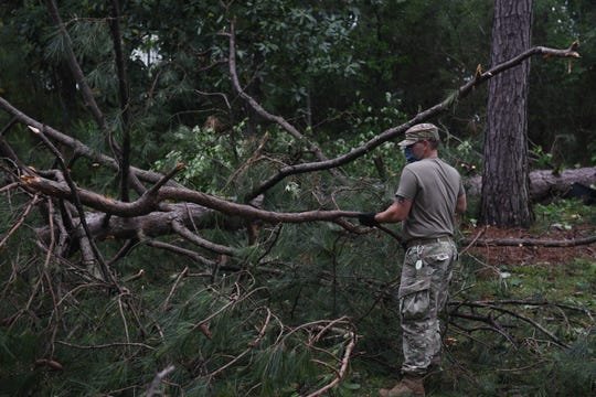 Spc. Clayton Dean, assigned to 3656th Ordnance Company, removes limbs from the campground at Camp Shelby Joint Forces Training Center, Monday, April 20, 2020. Seventy buildings received minor damage and two buildings major damage after a tornado tore through the Hattiesburg area Sunday, April 19, 2020.