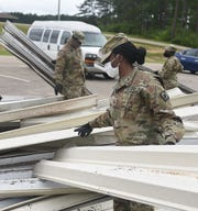 Sgt. Shaneice Wade, assigned to the Camp Shelby Installation Support Unit, moves a portion of the metal awning that once hung above the soldiers readiness processing site at Camp Shelby Joint Forces Training Center, Monday, April 20, 2020. Seventy buildings received minor damage and two buildings major damage after a tornado tore through the Hattiesburg area Sunday, April 19, 2020.