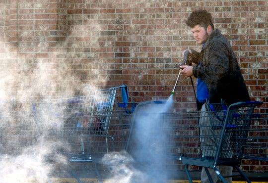 Sureway employee Zach Hayden sanitizes and pressure washes grocery carts outside Sureway North Tuesday morning. The carts have been sanitized every day and professionally cleaned twice a week since early March due to the spread of COVID-19.