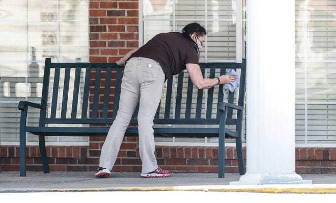 A worker sanitizes a trash can and bench outside the Homewood Health Campus assisted living facility, 2494 Lebanon St. in Lebanon Ind., Tuesday, April 21, 2020. The facility is shown during the hight COVID19 pandemic in Indiana.