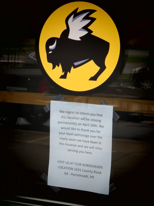A sign was taped to the front door of the Buffalo Wild Wings in Ithaca to inform customers that the business would close permanently.