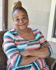 Toni Gibbs-Vanzant sits on the porch of her family's home in Jackson. Vanzant and her sister both retired from the health care field to take care of their mother.