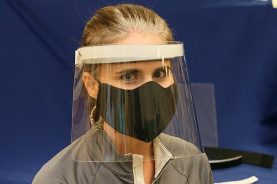 Luly Johnson of Methodist Orthotics & Prosthetics models the face shields being built in the Flowood clinic's lab.