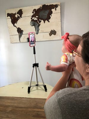 Heather Courville holds her daughter Capri up for her teletherapy appointment with physical therapists Jeanne Pichoff.