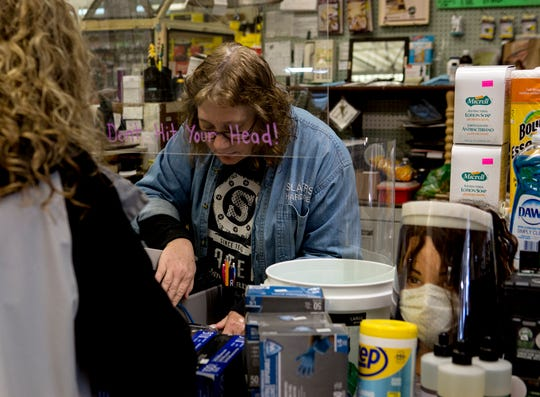 Darla Carpenter takes care of a customer at Slater's Hardware. The hardware store has put up glass at the register as well as a sign at the door instructing customers to wait for assistance to cut down on traffic in the store.