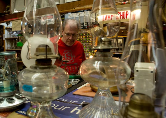 Shawn Hollingsworth works at his lamp station at Slaters Hardware which remains open during the pandemic. The hardware store has put up glass at the register as well as a sign at the door instructing customers to wait for assistance to cut down on traffic in the store.