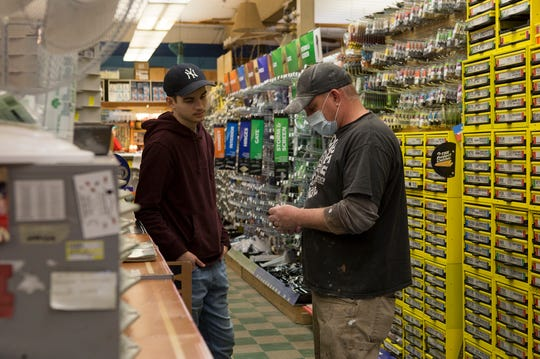 Nate Moreland helps a customer find the part he needs at Slaters Hardware which remains open during the pandemic. The hardware store has put up glass at the register as well as a sign at the door instructing customers to wait for assistance to cut down on traffic in the store.