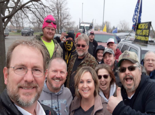 Howell congressional candidate Mike Detmer (left) received a death threat after posting this selfie that also shows a person wearing a Proud Boys mask and a Michigan Proud Boys sign in the background.