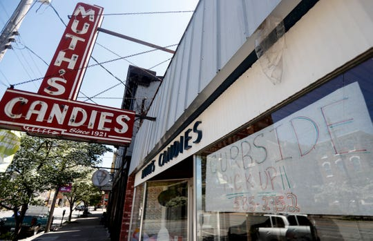 A sign on Muth's Candies on Market Street in NuLu lets customers know about curbside pickup.