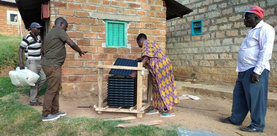 Joseph Kibaki (on left) of Agricycle helps train a woman In Muranga, Kenya,  on how to set up passive solar dehydrators so she can begin drying fruits.
