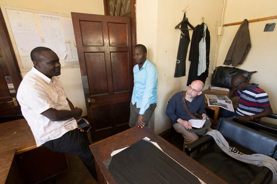OUTBREAK Milwaukee Journal Sentinel reporter Mark Johnson (scond from right) waits in an office with International Livestock Research Institution scientists James Akoko (left), Patrick Muinde, and Maurice Karani Thursday, January 12, 2017 at the public market in Nairobi, Kenya. Johnson was waiting for permisson to interview and photograph people at the butcher shops in the public market for a story on diseases that transfer from animals to humans.  MARK  HOFFMAN/MHOFFMAN@JOURNALSENTINEL.COM