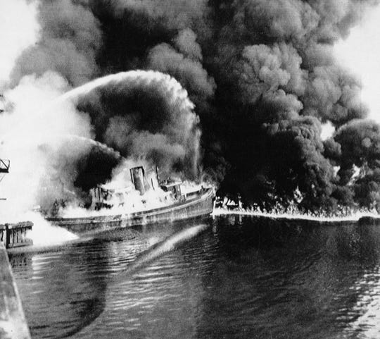 A fire tug fights flames on the Cuyahoga River near downtown Cleveland, where oil and other industrial wastes caught fire on June 25, 1952.