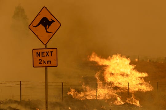 Fire burns in the grass near Bumbalong, south of the Australian capital of Canberra on Feb. 1. Earth Day has helped spur activism over issues like climate change, but monumental challenges remain.