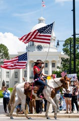 Shannon Andress rides a horse during the Stand Up Alabama Car Rally as it is held in front of the state capitol building in Montgomery, Ala., on Tuesday April 21, 2020. The rally is held in support of opening Alabama businesses during the coronavirus outbreak.