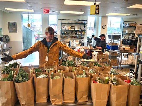 David Frease, procurement/sustainability manager at The Nashville Food Project, shows bags with fresh produce, dairy and eggs for the Community Cupboard project.