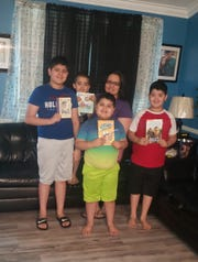 Linda Flores, center, president of the Cole Elementary School PTO in South Nashville, and her children pose with books they received recently from Nashville nonprofit Book'em. The nonprofit is giving away books at some Metro Schools food distributions while buildings are shut down during the pandemic. Left to right, Raul, 11, Luis, 5, Carlos, 6, Linda Flores, and Hector, 9.