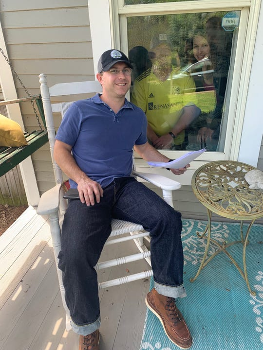 Warner Jones, an attorney with Carter Shelton Jones in Nashville, arranged to pass signatures through a window at the home ofRon and Erin Taylor to complete their estate planning.