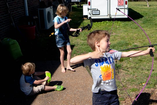 June, 10, Ryan, 6, and Luke Dotson shoot arrows outside their home Tuesday, April 21, 2020, in Dickson County, Tenn. The Dotsons do not have direct internet access to their home.