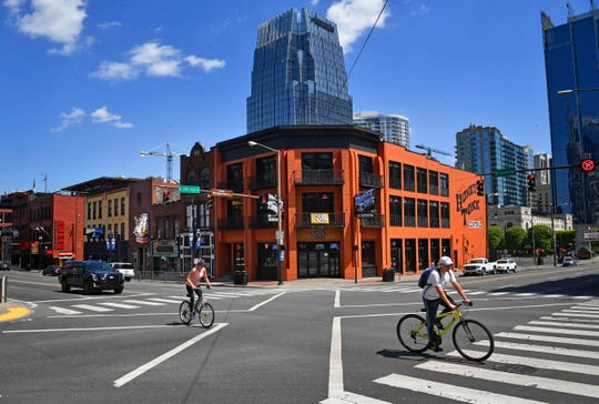 Bikes have plenty of room as they roam around downtown. Broadway at 4th is a shadow of it's former self because of COVID-19 in Nashville, Tenn. Monday, April 20, 2020.