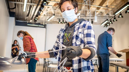 Student and faculty of Montclair State University's MIX Lab, along with community volunteers, assemble face shields for hospital workers.