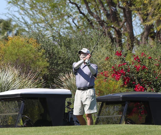 A golfer tees off with his face covered at Indian Ridge Country Club in Palm Desert as the course was one of the first to reopen, April 21, 2020.