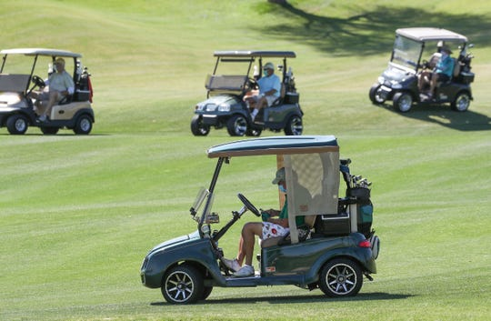 A foursome of golfers plays while riding in separate carts and playing with their faces covered at Indian Ridge Country Club in Palm Desert after the Riverside County of Public Health allowed golf courses to reopen, April 21, 2020.