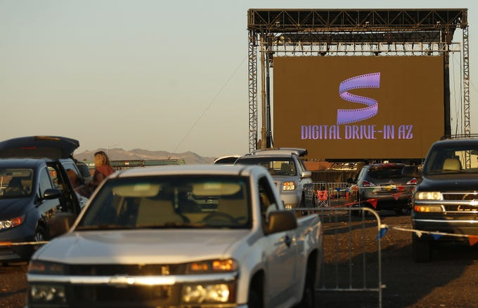 """People in their cars observe social distancing while watching the """"Book of Life,"""" an animated movie, at the Digital Drive-In AZ in Mesa, Ariz., on April 20, 2020."""