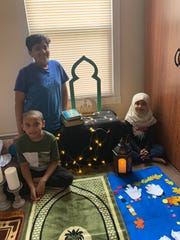 """Syed Ayyan, Syed Ammar and Abiha Asif in the """"masjid"""" their mother, Noreen Asif, created for them to celebrate Ramadan in their home in Marlboro."""