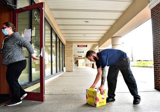 """Kayle Fry, right, of Manchester Township, picks up his purchase which was delivered curbside at Fine Wine & Good Spirits Premium Collection in Springettsbury Township, Tuesday, April 21, 2020. """"I put an auto dialer on my phone and just left it lay on my toolbox for about an hour and it just kept calling back every five seconds until it got through,"""" said Fry. Dawn J. Sagert photo"""