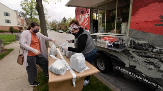 General manager Abbi Jo Ferree, right, hands a pre-ordered delivery to Thierry Gingrich, who came to bring some food back for her aunt who was craving Vampire Tacos.