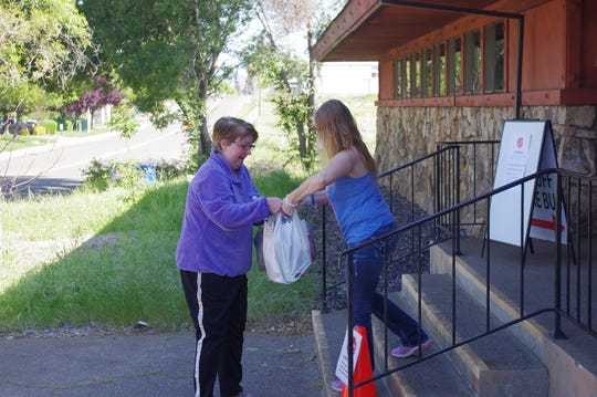 Kerrie Walter, right, a volunteer with the Salvation Army in Redding, hands out food to a client Tuesday.