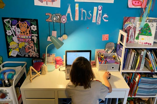 This April 9, 2020, photo released by Kara Illig shows her daughter, Ainslie Illig, 8, on her computer in Ebensburg, Pa. The frustration of parents is mounting as more families across the U.S. enter their second or even third week of total distance learning, and some say it will be their last. (Kara Illig via AP)