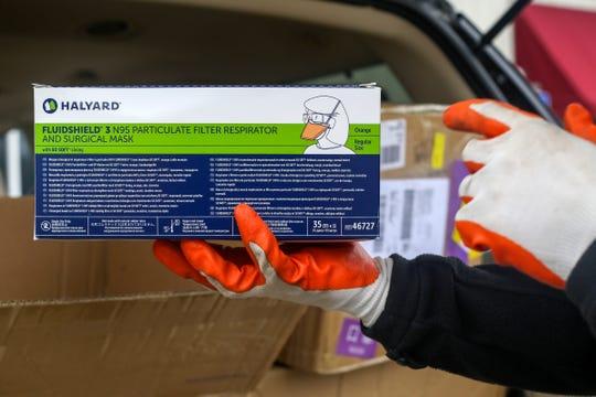 Oregon Chinese Coalition board member Hongcheng Zhao unpacks boxes of masks at Salem Fire Department Station 6 in Salem on April 21, 2020.