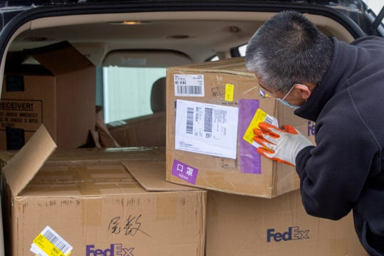 Oregon Chinese Coalition board member Hongcheng Zhao unpacks boxes of masks donated at Salem Fire Department Station 6 in Salem on April 21, 2020.