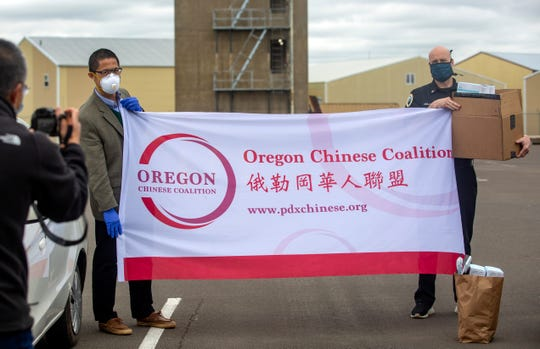 Oregon Chinese Coalition board member Hongcheng Zhao takes a picture of fellow board member Qusheng Jin and Captain Brian Hollis at Fire Department Station 6 in Salem on April 21, 2020.