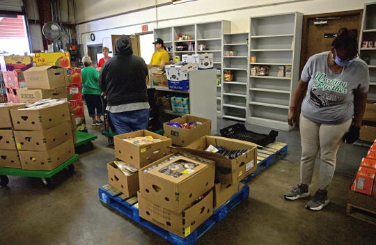 Workers at the Concho Valley Regional Food Bank in San Angelo prepare food for distribution to those in need Monday, April 20, 2020.