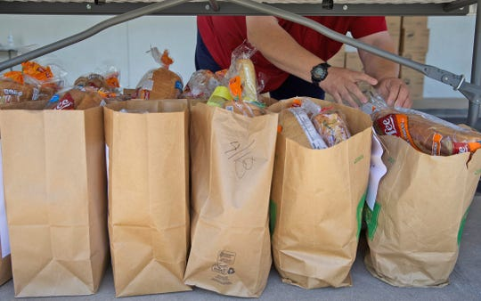 A volunteer at St. Paul Presbyterian Church in San Angelo prepares food for distribution to those in need Monday, April 20, 2020.