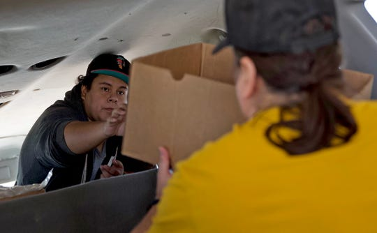 Raymond De La Garza, left, and Marcisso Leaton, right, with the Freedom Fellowship Church, load food for distribution to those in need at the Concho Valley Regional Food Bank on Monday, April 20, 2020.