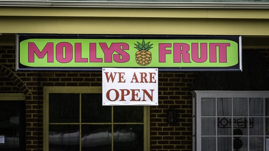 Several businesses in the Four Corners Plaza in Onley such as Mollys Fruit have signs prominently announcing  that they are open amid all the closures due to the coronavirus pandemic.
