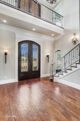 The home's lovely two-story entry features massive iron and glass double doors.